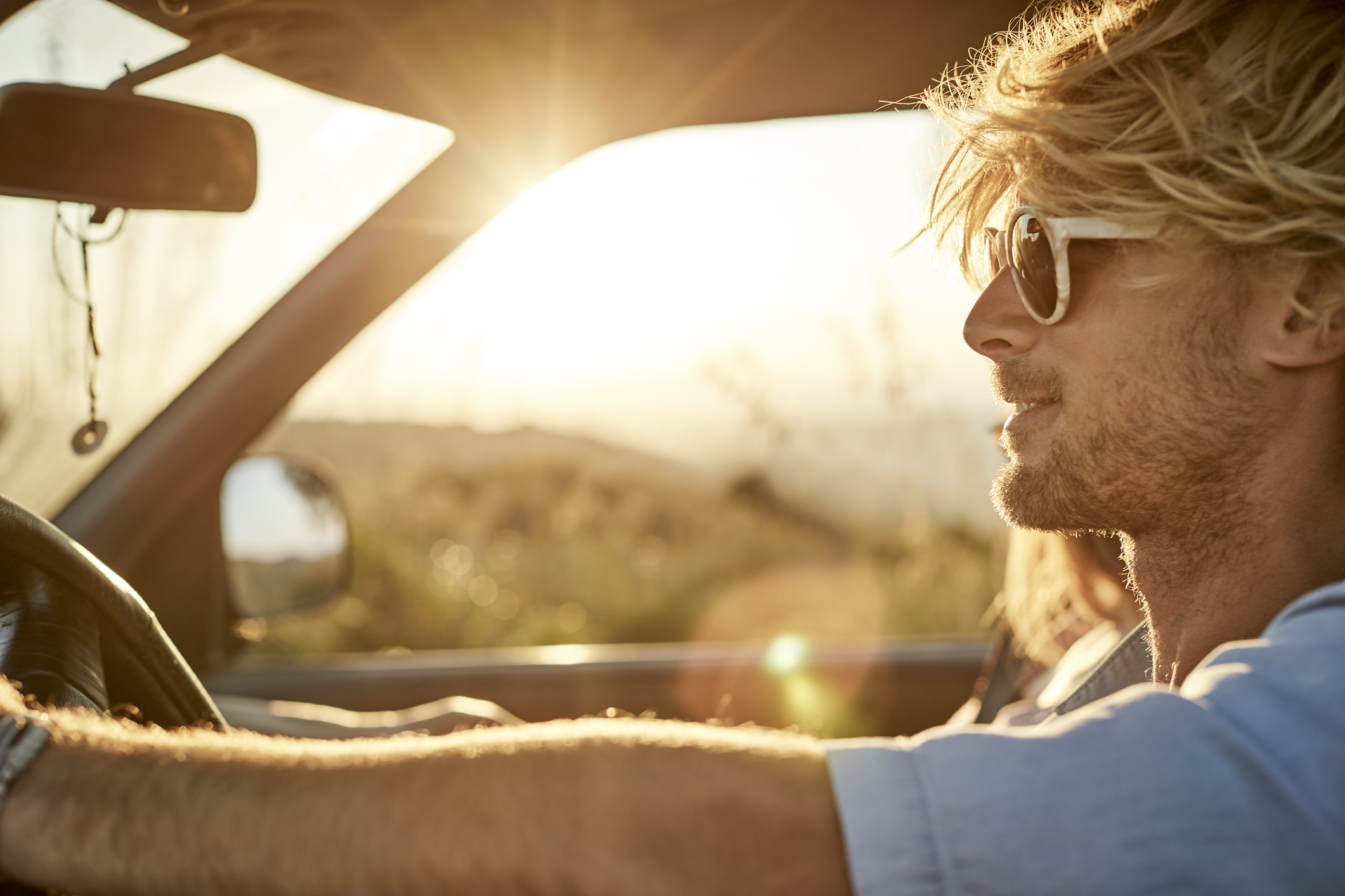Blonde man driving into the sunlight appreciating his low-interest auto loan.